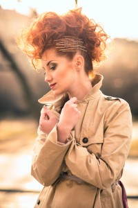 Beautiful red haired woman with cool hairstyle posing outdoors