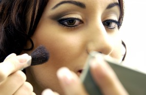 Close-up of a young woman putting on makeup